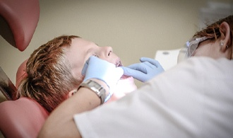 dentist examining little boy's mouth