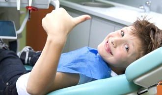A young patient giving a thumbs-up at their dental appointment.