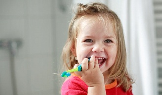 toddler girl holding a toothbrush