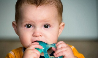 toddler boy chewing on blue teething ring