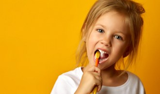 little girl brushing her teeth against yellow background