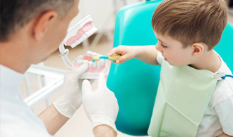 Child in dental chair practicing tooth brushing on model