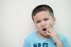 little boy holding jaw from toothache
