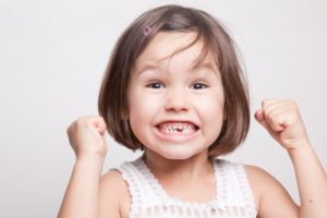 Excited girl with missing tooth smiles at her Hillsboro pediatric dentist