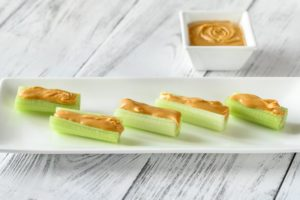 Cuts of celery topped with peanut butter on a white plate sitting on a white wooden table
